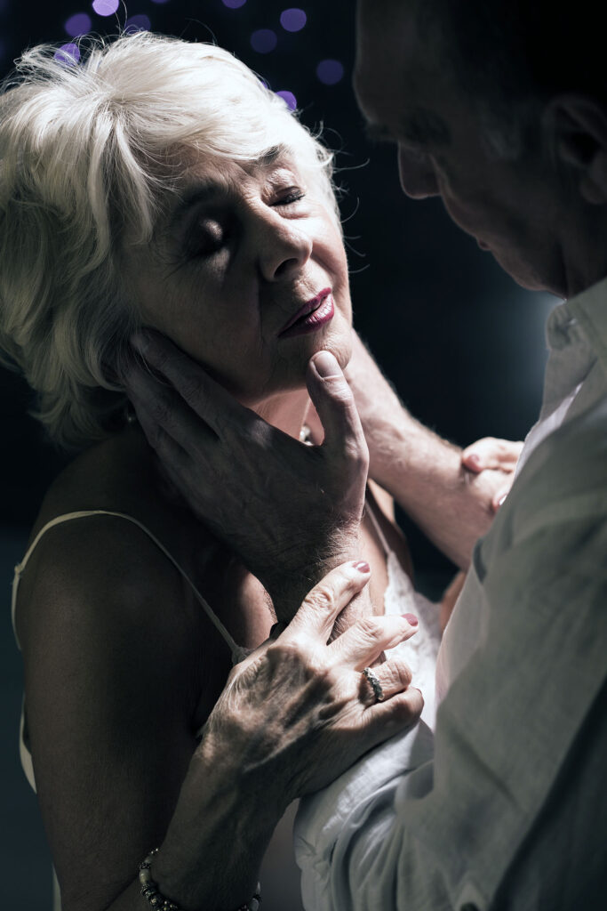 Elder man taking the senior adult woman's face in his hands in a very sexy way