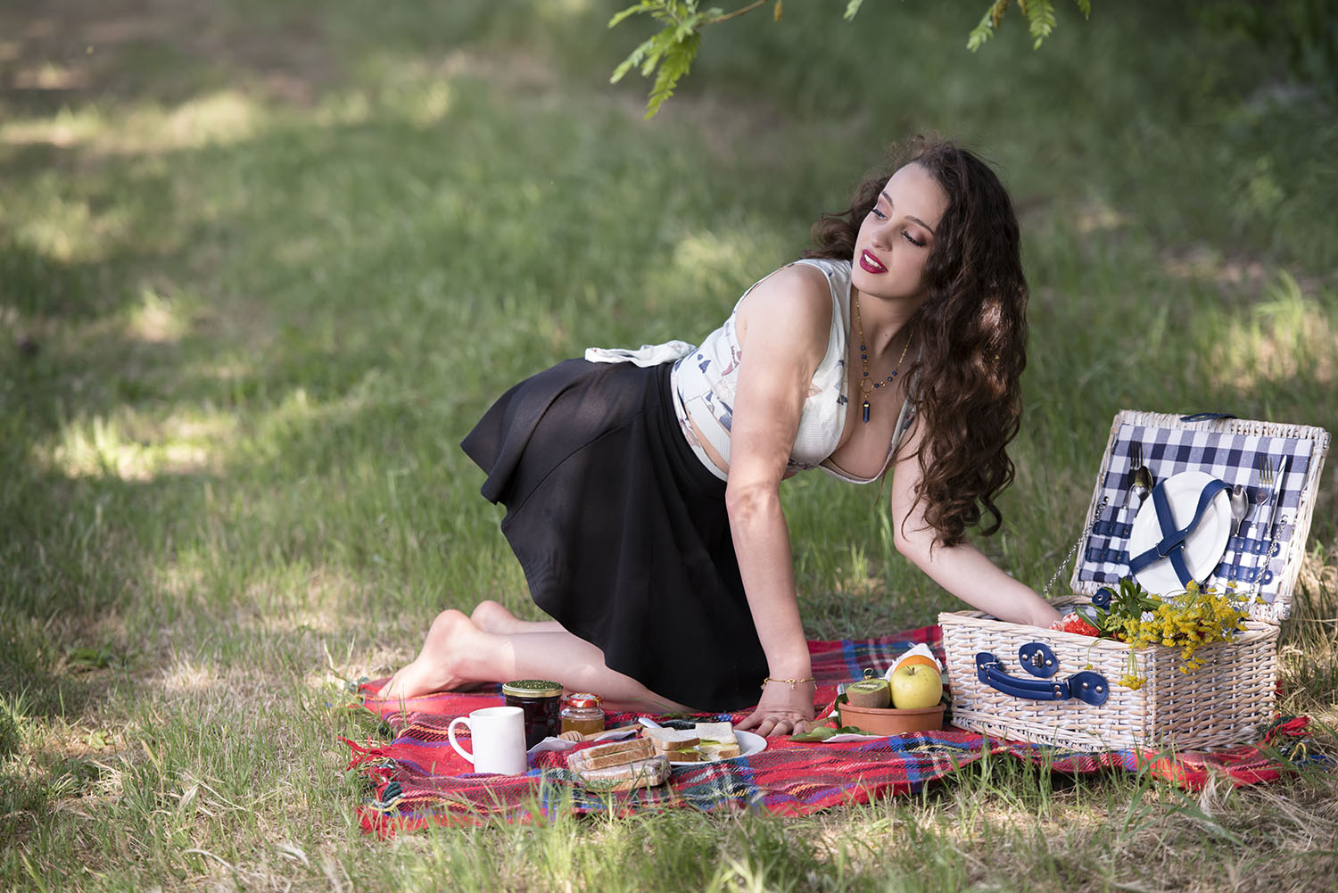 young beautiful woman having a picnic, wearing a skirt and a sexy deep neckline blouse, preparing her meal