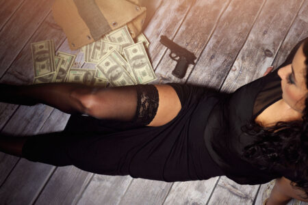 Beautiful girl in a black dress with sideslip sitting on the floor in stockings with money and a gun spread out on the floor around her