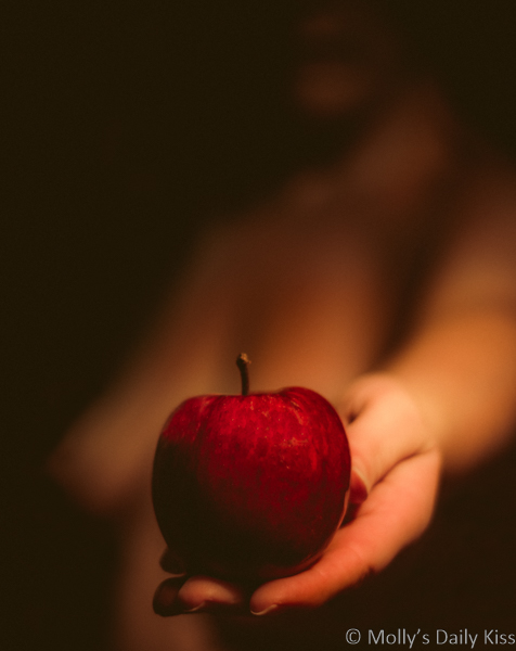 Naked woman in soft lit shadows holding an apple in front of her. the apples is the only thing in focus.