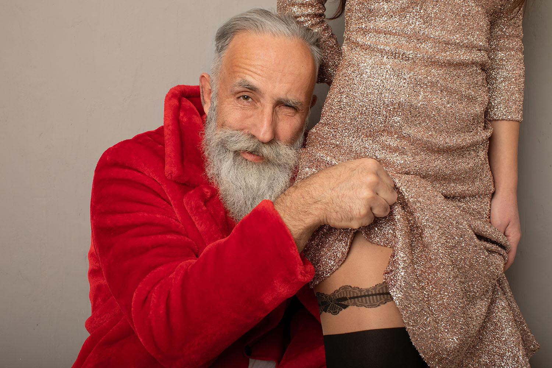 Passionate couple, bearded senior man lifts up dress of sexy woman