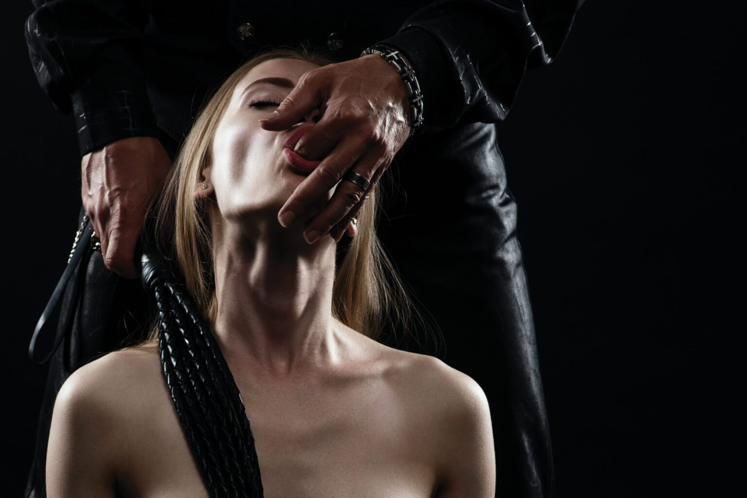 couple playing sexual games- man's finger in submissive's mouth